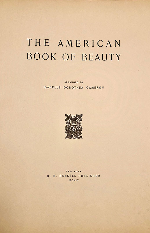 The title page for The American Book of Beauty on yellowed paper. In black text it reads The American Book of Beauty arranged by Isabelle Dorothea Cameron. Below this in the center of the page is a printer's mark that is a black rose with RR printed in the rosebud. At the bottom of the page is the imprint, also in black, which is text that gives publication information.