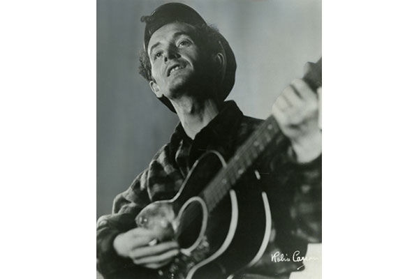 Black and white photograph of Woody Guthrie playing the guitar.