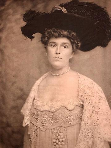 A sepia tinted portrait of a woman looking directly at the camera, visible from the waist up in front of a plain background. She wears a white lace loose bodice dress with a square neck, embroidered detail and draped lace sleeves, a white pearl necklace that sits tightly around her neck, a large dark hat with an equally large plume of the same color, and her hair in an updo.
