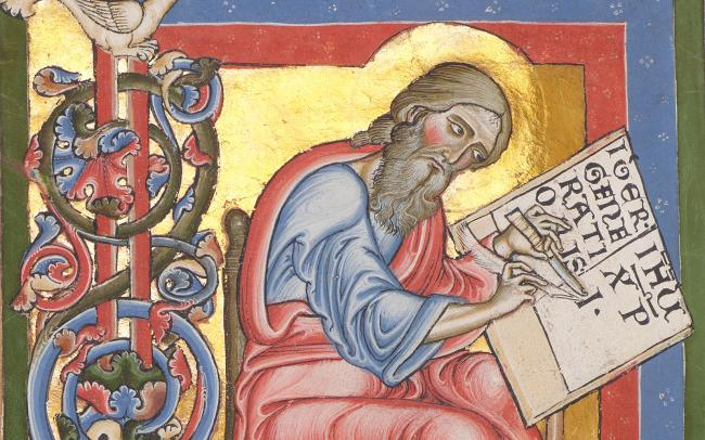 Seated bearded male figure in light red and blue robes scribing a manuscipt with feather pen with gold leaf, red, blude and green backfround and filigree pattern to the left.