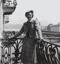 Felice Stampfle standing on a balcony with a river scene behind her.