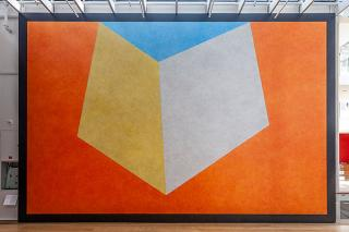 Photograph of mural with orange, yellow and blue geometric shapes.